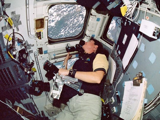 Racine native and UW alum Laurel Clark looks out the window of Space Shuttle Columbia in 2003. Clark, a physician, conducted experiments in space including gravity and its effect on humans and gene transfer of plants growing in zero gravity.