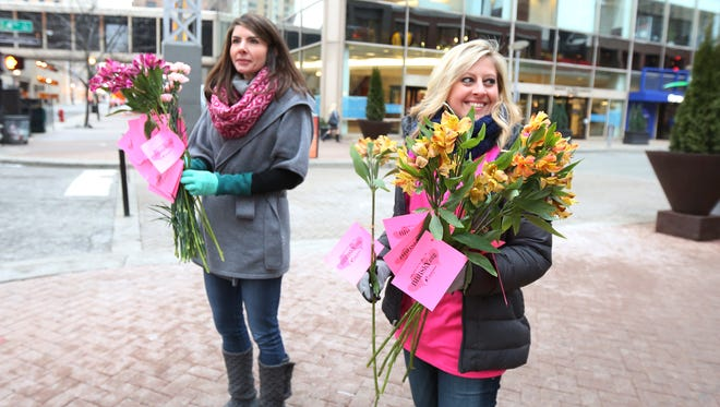 Jessica Klein, left, and Amy Smith with Big Brothers Big Sisters of Kentuckiana hand out flowers at Fourth Street Live! on Friday morning.  The flowers were donated by Nanz & Krafts.  Each flower had a note on it reminding recipients of the need for Big Brother and Big Sister volunteers in the area. February 12, 2016