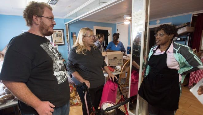 Sylvia Tisdale, pastor of Epps Christian Center, right, talks with Wylie Wilferth, and Trinkette Haines, during their visit to the food bank Tuesday, Oct. 31, 2017. The Pace Blvd. food bank is running low on food staples as the holiday season approaches.