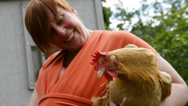 Tanya Keith holds one of her seven backyard chickens at her home in Des Moines.
