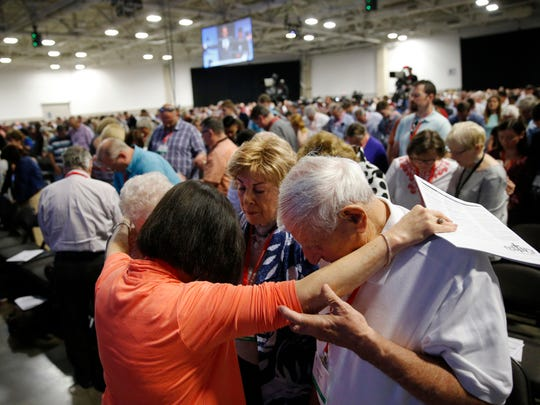 Cindy Boto (bottom left), Peggy Hott, slightly hidden, Pat King-Boto, center facing camera, and August Boto, far right, pray as a group amongst others during a time of prayer at the 2018 Annual Meeting of the Southern Baptist Convention at the Kay Bailey Hutchison Dallas Convention Center in Dallas on Tuesday, June 12, 2018.