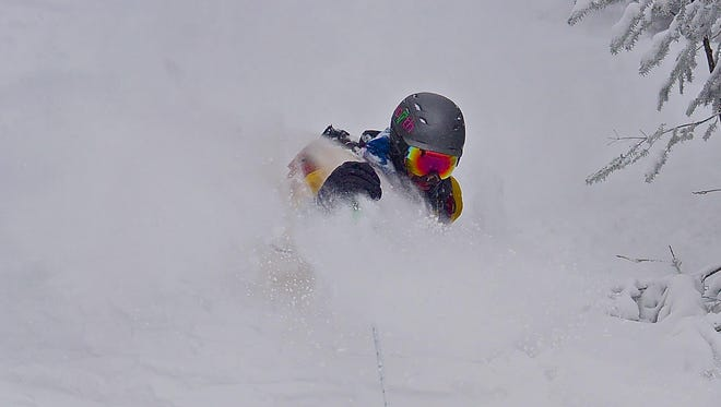 Dalton Harben of Cambridge bursts through deep powder snow at Smugglers' Notch Resort. Harben said he has trouble skiing firm snow at resorts due to a serious injury he suffered while backcountry skiing on Mount Washington.