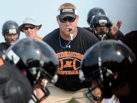 Northeastern football coach Jon Scepanski runs his team through hitting drills during the first day of fall practice at the high school on Monday, August 17, 2015.