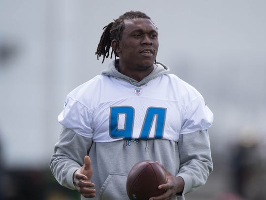 Lions defensive end Ziggy Ansah watches drills during