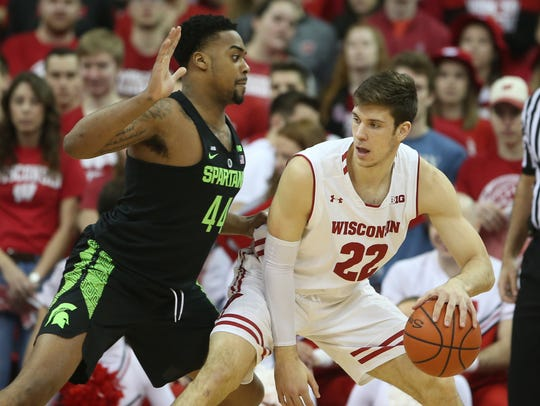 Wisconsin forward Ethan Happ dribbles against MSU forward Nick Ward on Sunday.