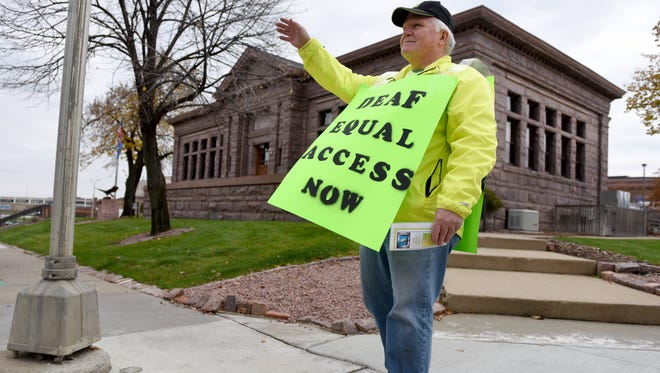 Barry Carpenter waves to motorists at the corner of Dakota Ave. and 10th Street in downtown Sioux Falls on Thursday, Oct. 20, 2016. Carpenter and other volunteers with the Deaf Grassroots Movement - South Dakota held a rally to raise awareness for the equal rights of deaf voters.