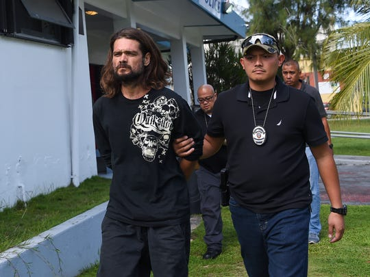 Robert Isaac Revels is escorted from the Guam Police