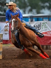 Tiany Schuster competes in the barrel racing event during the Big Sky Pro Rodeo at the Montana State Fair Wednesday evening.
