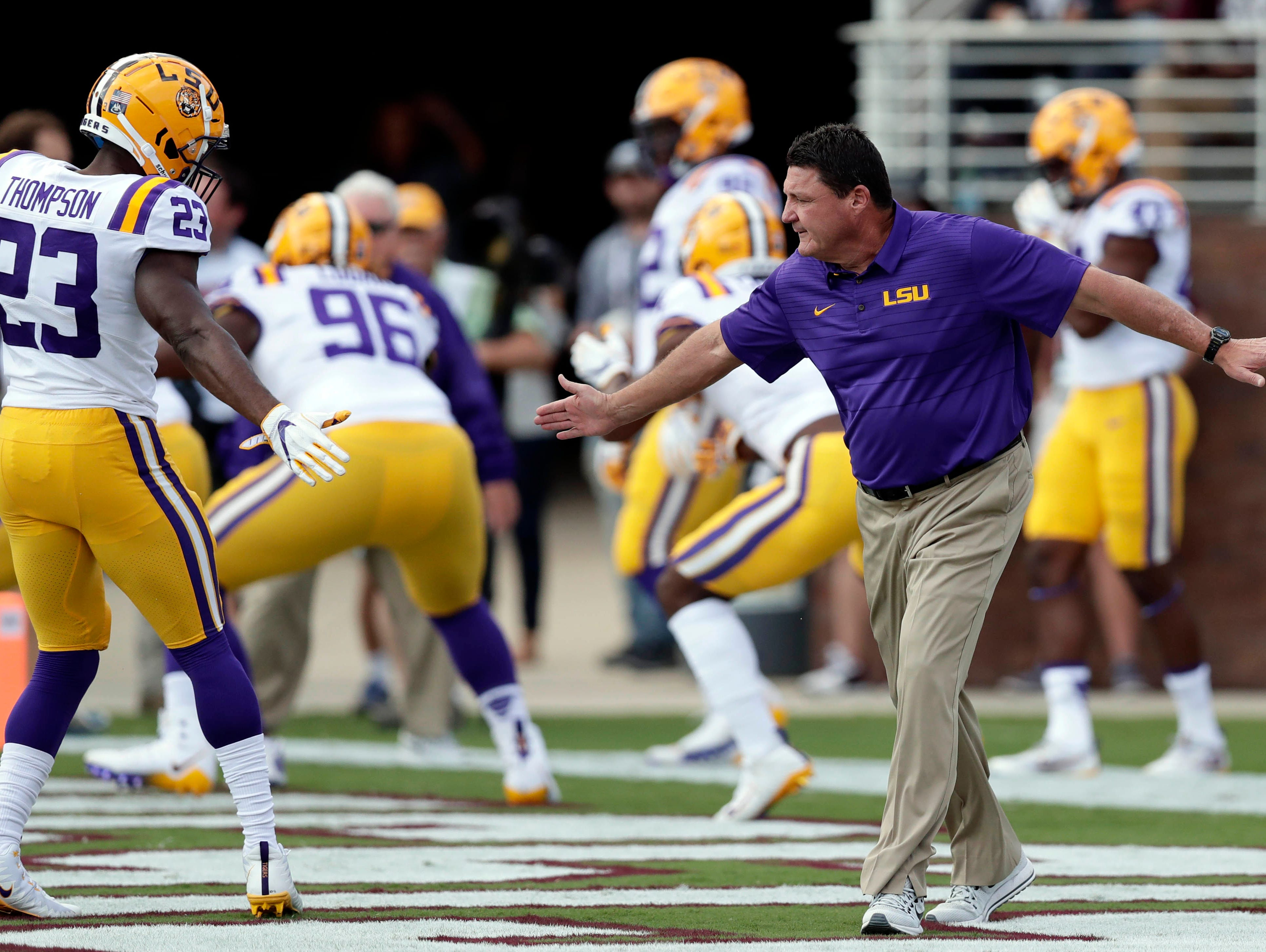 LSU head coach Ed Orgeron reaches out to LSU linebacker Corey Thompson (23) during the pregame warm up drills prior to their NCAA college football game against Mississippi State in Starkville, Miss., Saturday, Sept. 16, 2017.