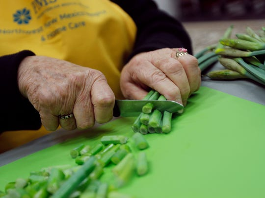 A volunteer cuts the stems off a bunch of daffodils Thursday at the First Presbyterian Church in Farmington.