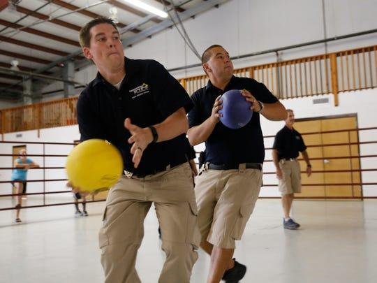 Farmington Police School Resource Officers Shawn Goodsell and Kris Chavez play dodgeball Aug. 29 at the 4 Corners MessFest at McGee Park.