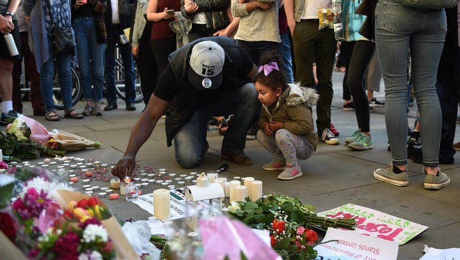 Mourners in Albert Square in Manchester on May 23, 2017, after a vigil for those killed and injured in the May 22 terror attack at the Ariana Grande concert at the Manchester Arena.