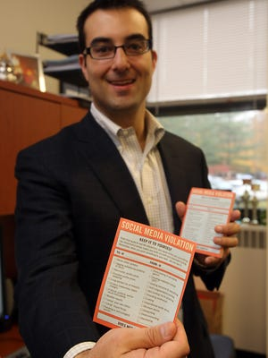 Christopher Salute, who teaches a social media course at Mercy College, shows the social media notes he gives his students in his office in Dobbs Ferry.