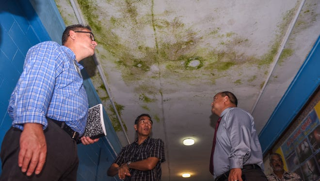 Education officials look up at algae and mold growing at a moist section of ceiling in a hallway at V.S.A. Benavente Middle School on Tuesday, June 6, 2017. Guam Department of Education Superintendent Jon Fernandez took a tour of the school to determine what repairs or improvements would need to be addressed before the start of the next school year. From left: Christopher Anderson, GDOE student support services administrator; Dennis Malilay, Benavente Middle School assistant principal and Fernandez.