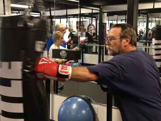 Rock Steady Boxing participant punching the heavy bag.
