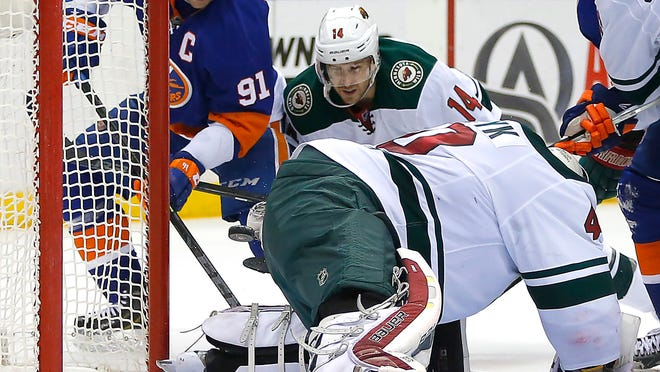 Islanders center John Tavares, left, scores a goal as Minnesota Wild goalie Devan Dubnyk goes down and Justin Fontaine watches during the second period. The Wild won 2-1 in a shootout.