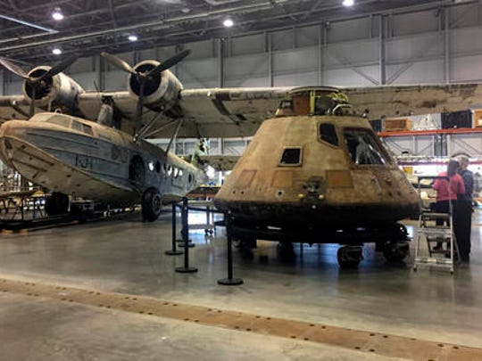 In this photo taken Feb. 17, 2017, the Apollo 11 capsule sits in the restoration hanger at the National Air and Space Museum's Steven F. Udvar-Hazy Center in Chantilly, Va., ahead of a planned four-city tour. The Apollo 11 command module, which travelled more than 950,000 miles to take Americans to the moon and back in 1969, is going on a road trip, leaving the Smithsonian for the first time in more than four decades. The airplane at left is the only aircraft in the Smithsonian's collection that was stationed at Pearl Harbor on Dec. 7, 1941, the day the naval base at the harbor was attacked by Japan.