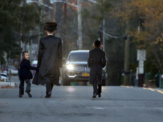 A man walks with two young boys on Herrick Avenue in Ramapo before the start of Sabbath.