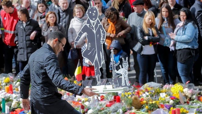 People gather to commemorate the victims of the March 22, 2016, terror attacks, at the site of a memorial in Place de la Bourse, Brussels, Belgium.