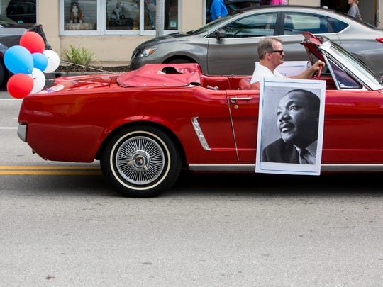 A photo of Rev. Dr. Martin Luther King Jr. hangs from the side of a car during the 20th Annual Rev. Dr. Martin Luther King Jr. Parade and Celebration in downtown Naples on Monday, Jan. 16, 2017.