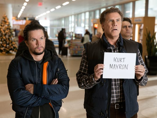 Mark Wahlberg, left, as Dusty and Will Ferrell as Brad wait at the airport for their fathers in 'Daddy's Home 2.'