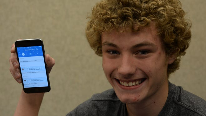 Braedon Coates holds an iPhone running the Upto app at Test Intermediate School in Richmond.