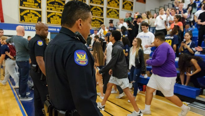 Phoenix Police officers keep control of the crowd at a recent high school basketball game in Arizona.