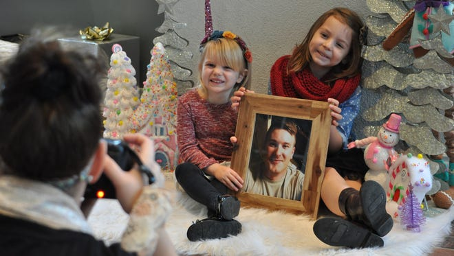 Sisters Madelyn Friedrich, 5, and Harper, 3, pose with a picture of their deployed dad during Fort Polk's 2015 Very Merry Military Mini Sessions, held Saturday.