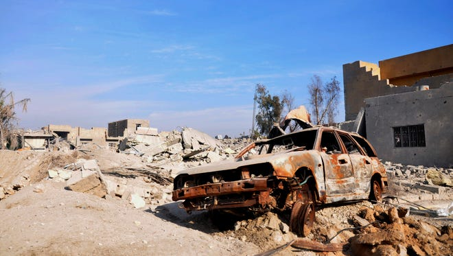A burned out car lies amid damaged buildings in Ramadi, Iraq, on Jan. 2, 2016.