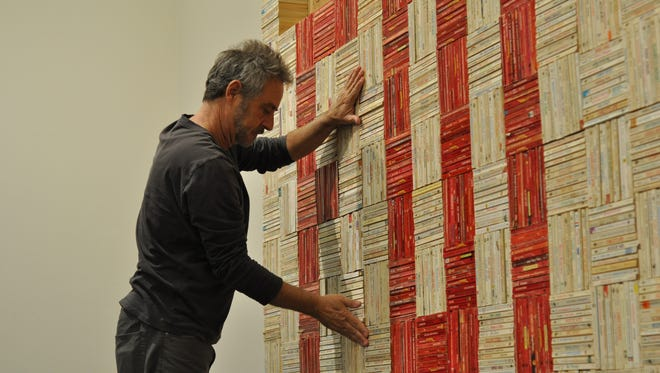 "John Salvest puts together his sculpture, made from 4,000 paperback romance novels, on Friday morning at the Alexandria Museum of Art. Once completed, the darker colored books spell out the word ""forever."""