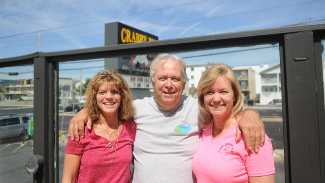 Crabby Pig owner Terry Crawford smiles with his general manager Christina Michael (left) and his floor manager Deanna Bridell (right).