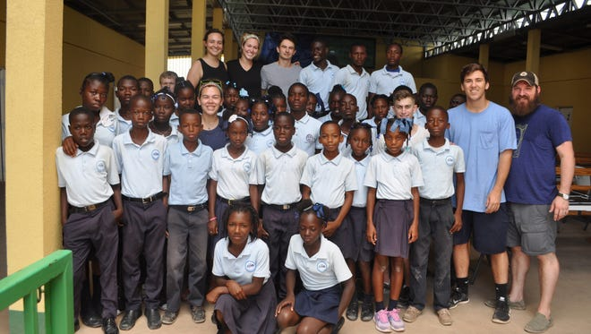 Sixth-grade students at the Respire Haiti school celebrate receiving new computers with alumni from St. Thomas More Catholic High School.