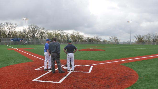 Forsyth baseball coach Jim Julian (pictured at left, in blue) oversaw installation of a multipurpose artificial playing field at Forsyth High School, which opened in 2014.