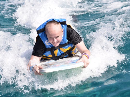Bethany Gruich of Lamoni rides the waves during a Make-A-Wish trip to the Caribbean in 2013.