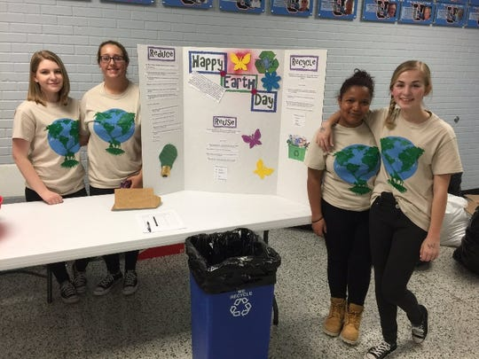 Kendra McDowell, Tori Collins, Kaylee Boyd, and Lilly Shirel show off their Earth Day project encouraging recycling.