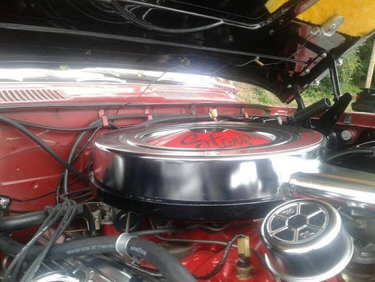 An engine sits in the open hood of a car Sunday. There