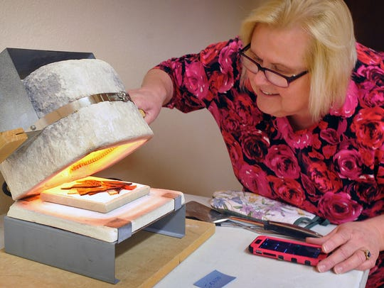 Stained glass artist Debbie Malone checks on a fused