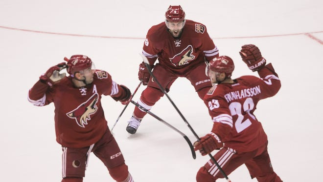 Coyotes' Sam Gagner screams as Keith Yandle (L) and Oliver Ekman-Larsson react to a game-winning goal from Ekman-Larsson at Gila River Arena in Glendale, AZ on Saturday, Oct. 25, 2014.