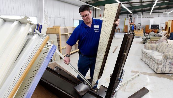 Mark Phillips, manager of the Central Minnesota Habitat for Humanity ReStore, assembles shelves Tuesday, Feb. 2, 2016 as volunteers move items back on the show room floor. The store had been closed while the interior was remodeled.