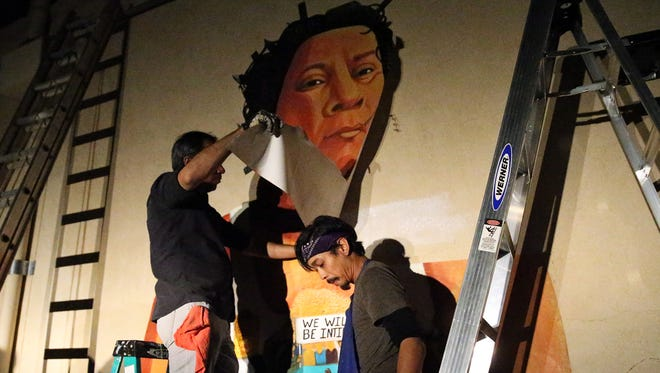 """Artist Ramon Cardenas, right, gets help from Juan Saldivar attaching a mural made of acrylic on polytab material depicting the late Chicano activist Oscar """"Zeta"""" Acosta on the wall of a building at Texas and North Ochoa Street Thursday night. Cardenas and fellow artist Christian Cardenas produced the mural."""