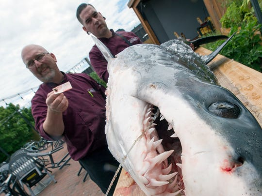Executive chef Jim Switzenberg, left, with sous chef Travis Markel, check out the 162-pound shark.