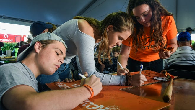 """Hunter Holmes, 14, (left); Kalani Keane, 15, (center); and Emilia Zaragoza, 14, all of Fort Pierce, write messages of love and encouragement to Layne Chesney Wednesday, Jan. 24, 2018, during the """"For the love of Layne!"""" fundraiser to support Layne Chesney and her family at Big Apple Pizza on South 35th Street in Fort Pierce. Chesney, 14, suffered burns over 95% of her body from a New Year's Eve incident. Proceeds from all food and beverages sold, along with all staff salaries and tips, will benefit Layne and her family. To see more photos, go to TCPalm.com."""