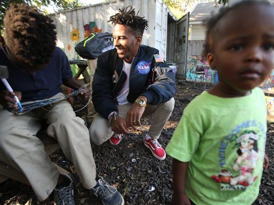 Artist Lawrence Matthews III, center, watches children