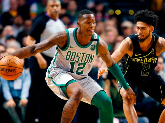 FILE - In this April 8, 2018 file photo, Boston Celtics' Terry Rozier (12) keeps the ball away from Atlanta Hawks' Tyler Dorsey (2) during the second quarter of an NBA basketball game in Boston.  The Celtics enter the playoffs as the East's No. 2 seed after a season filled with devastating injuries, beginning with Gordon Hayward's ankle injury in the season opener. But with Kyrie Irving's recent knee surgery landing him on the sideline as well, it has an already-hobbled Boston team looking very vulnerable against a seventh-seeded Bucks team led by Giannis Antetokounmpo.  (AP Photo/Michael Dwyer)