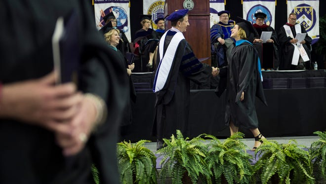 UE President Thomas Kazee hands out diplomas during the University of Evansville graduation ceremony at the Ford Center on Saturday, May 5, 2018.