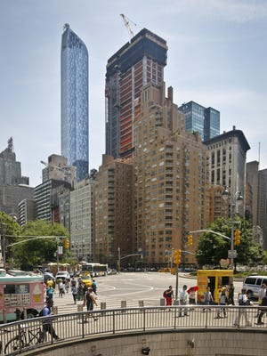 A luxury, 90-floor apartment skyscraper called One57, left, rises above all other buildings overlooking Central Park, while a crane sits atop ongoing construction for a new condominium skyscraper at 220 Central Park South, on Thursday in New York.