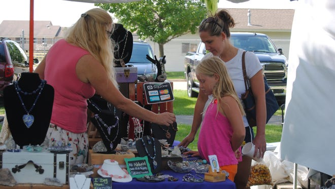 Megan McShane and daughter Grace Field, 8, of Marysville, peruse pieces of Donna Peterson's in Peterson's booth for her Bella Donna's Baubles business on Saturday, Aug. 20, 2016, in Marysville Park.