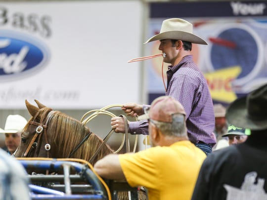 A roper competes in preliminary roping events for the