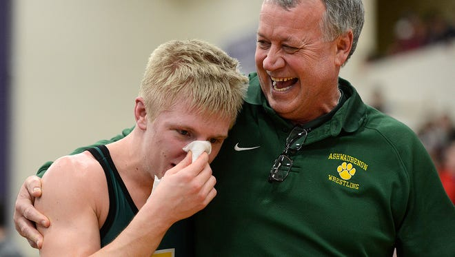 Ashwaubenon's Zac Benton is congratulated by coach Jody Van Laanen after Benton defeated Pulaski's Jake Gille in the 138-pound championship match during Saturday's WIAA Division 1 wrestling sectionals at Green Bay West High School.
