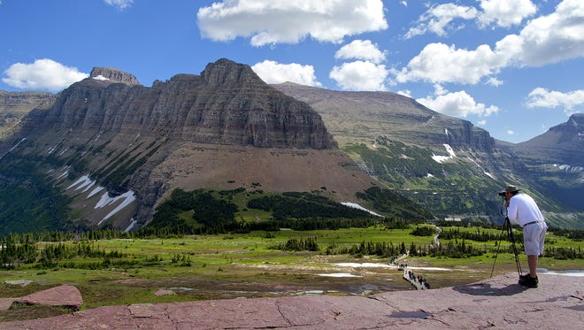 A visitor to Glacier National Park takes a photograph of the Garden Wall at Logan Pass.